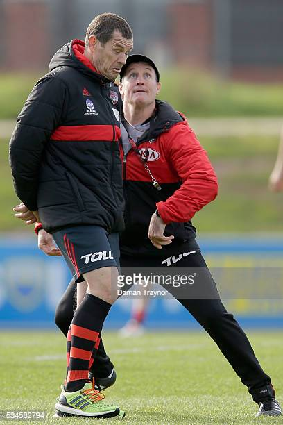 John Worsfold Senior Coach of the Bombers keeps his eyes on a ball as assistant coach Mark Harvey ducks for cover during an Essendon Bombers...