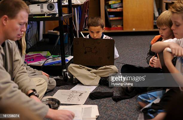 John Wysong left checks with spellings with Sebastian Nadeau second left and 4th grade students at Fremont Elementary School March 10 2011 Hyoung...
