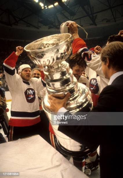 John Ziegler president of the NHL awards the Stanley Cup Trophy to Denis Potvin of the New York Islanders as teammate Butch Goring celebrates their...