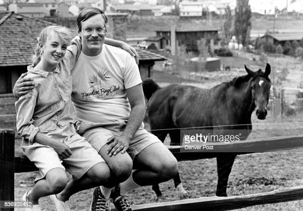 Johna and Kirby Gray sit on the fence of their home in Southeast suburb of Denver to the right is the family horse they also have a donkey dogs cats...