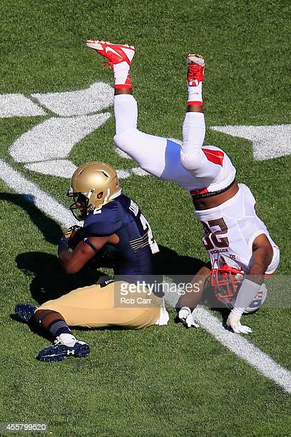 Johnathan Aiken of the Rutgers Scarlet Knights flips over Parrish Gaines of the Navy Midshipmen while making a tackle on a first half punt return at...