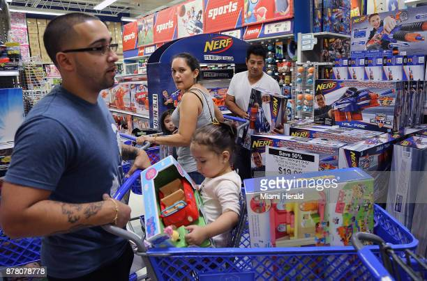 Johnathan Beauchamp left and daughter Alaya squeeze by fellow shoppers Diana Barrios center and husband Pablo Barrios right scramble for deals as...