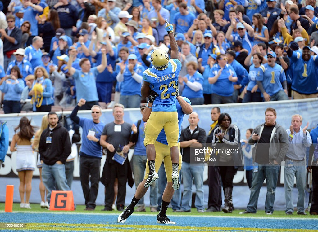 Johnathan Franklin #23 of the UCLA Bruins celebrates his touchdown with fans as he is lifted by Joseph Fauria #8 during a 38-28 win over the USC Trojans at Rose Bowl on November 17, 2012 in Pasadena, California.