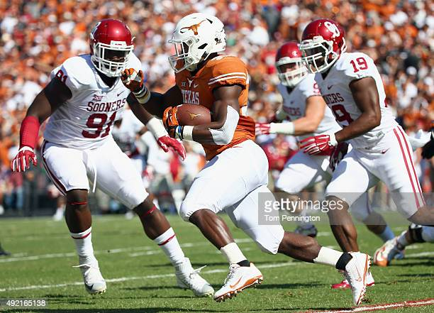 Johnathan Gray of the Texas Longhorns carries the ball against Charles Tapper of the Oklahoma Sooners and Eric Striker of the Oklahoma Sooners in the...