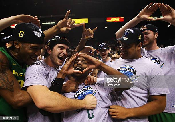 Johnathan Loyd of the Oregon Ducks celebrates with teammates after they defeated the UCLA Bruins 78 to 69 in the Pac-12 Championship game at MGM...