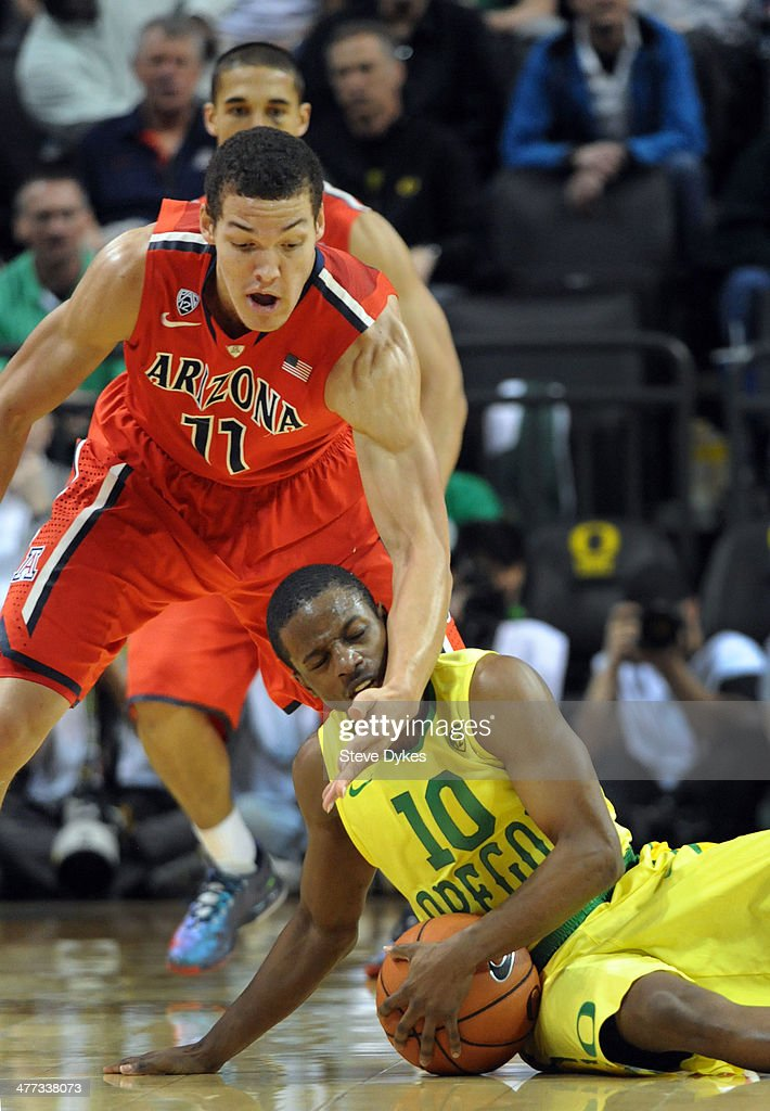 Johnathan Loyd #10 of the Oregon Ducks is fouled by Aaron Gordon #11 of the Arizona Wildcats during the second half of the game at Matthew Knight Arena on March 8, 2014 in Eugene, Oregon. Oregon won the game 64-57.
