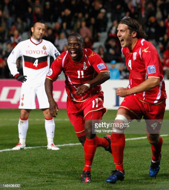 Johnathan McKain of Adelaide United celebrates scoring the first goal with team mate Bruce Djite during the AFC Asian Champions League match between...