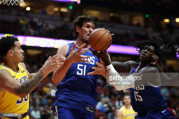 Johnathan Motley and Boban Marjanovic of the LA Clippers battle Jeffrey Carroll of the Los Angeles Lakers for a rebound during the second half of a...