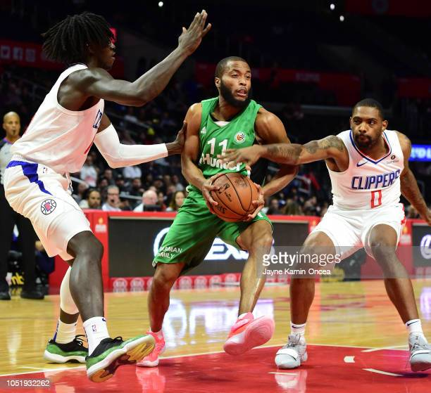 Johnathan Motley and Sindarius Thornwell of the Los Angeles Clippers guard Tre Kelley of Maccabi Haifa as he drives to the basket in the second half...