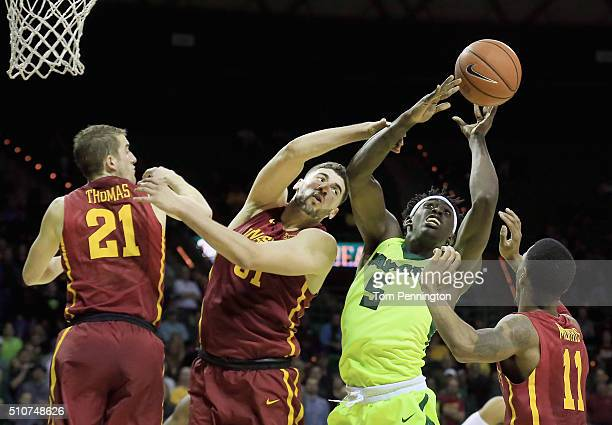Johnathan Motley of the Baylor Bears rebounds the ball against Matt Thomas of the Iowa State Cyclones Georges Niang of the Iowa State Cyclones and...