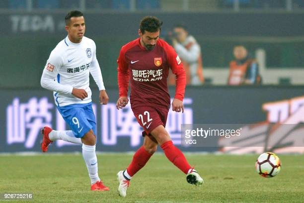 Johnathan of Tianjin Teda and Ezequiel Lavezzi of Hebei China Fortune compete for the ball during the 2018 Chinese Football Association Super League...
