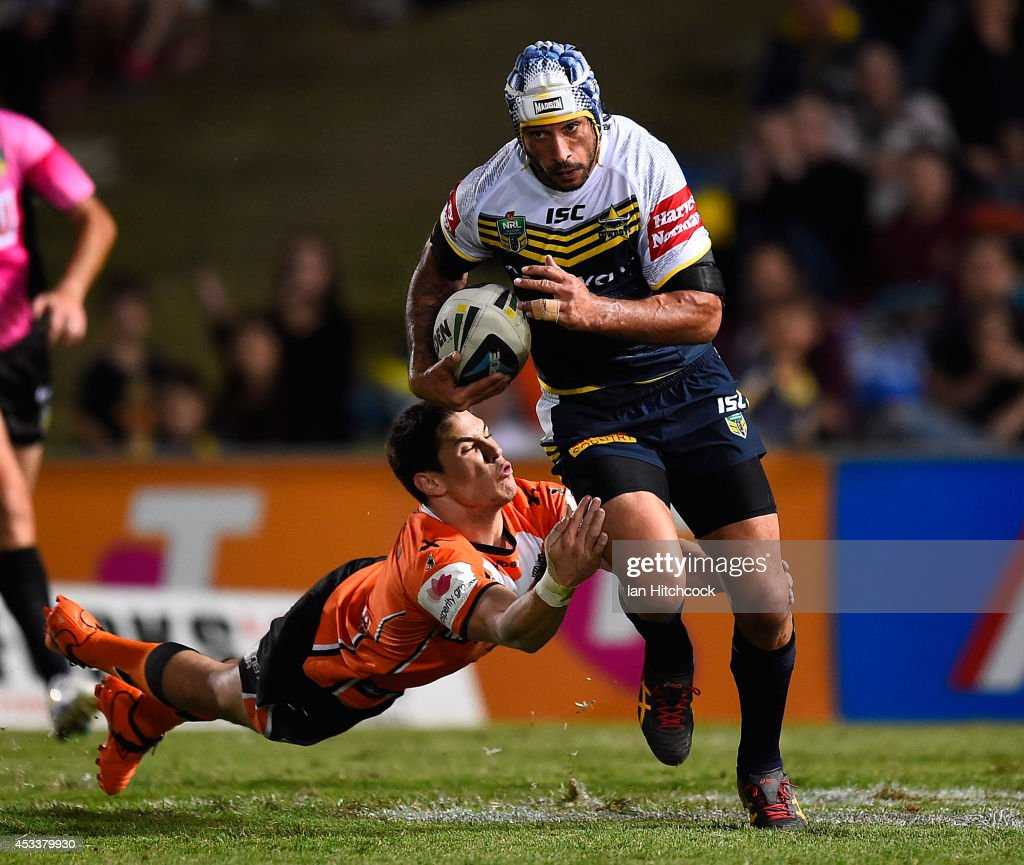 Johnathan Thrston of the Cowboys skips out of the tackle of Mitchell Moses of the Tigers during the round 22 NRL match between the North Queensland Cowboys and the Wests Tigers at 1300SMILES Stadium on August 9, 2014 in Townsville, Australia.