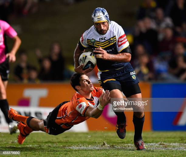Johnathan Thrston of the Cowboys skips out of the tackle of Mitchell Moses of the Tigers during the round 22 NRL match between the North Queensland...