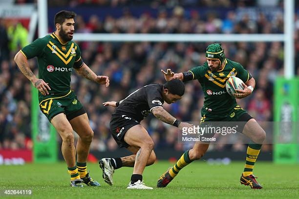 Johnathan Thurston of Australia keeps Issac Luke of New Zealand at arms length during the Rugby League World Cup Final between Australia and New...