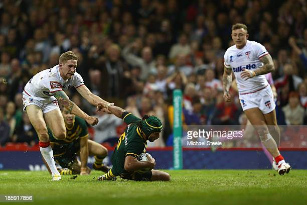 Johnathan Thurston of Australia scores his sides opening try as Sam Tomkins of England closes in during the Rugby League World Cup Group A match...