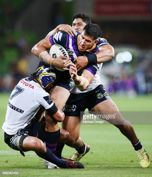 Johnathan Thurston of the Cowboys and John Asiata tackle Nelson Asofa Solomona of the Storm gets tackled during the round three NRL match between the...