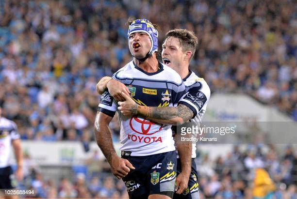 Johnathan Thurston of the Cowboys celebrates a try by team mate Gavin Cooper during the round 25 NRL match between the Gold Coast Titans and the...