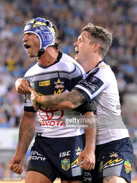 Johnathan Thurston of the Cowboys celebrates a try by team mate Gavin Cooper after the round 25 NRL match between the Gold Coast Titans and the North...