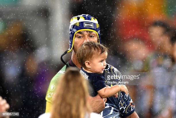 Johnathan Thurston of the Cowboys enters the field of play with his young child during the NRL trial match and Jonathan Thurston/Cameron Smith...