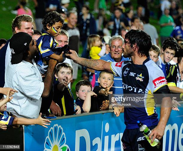 Johnathan Thurston of the Cowboys gives his headgear to a child in the crowd after wining the round six NRL match between the North Queensland...