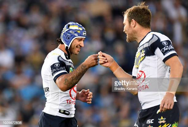 Johnathan Thurston of the Cowboys greets team mate Gavin Cooper before the round 25 NRL match between the Gold Coast Titans and the North Queensland...