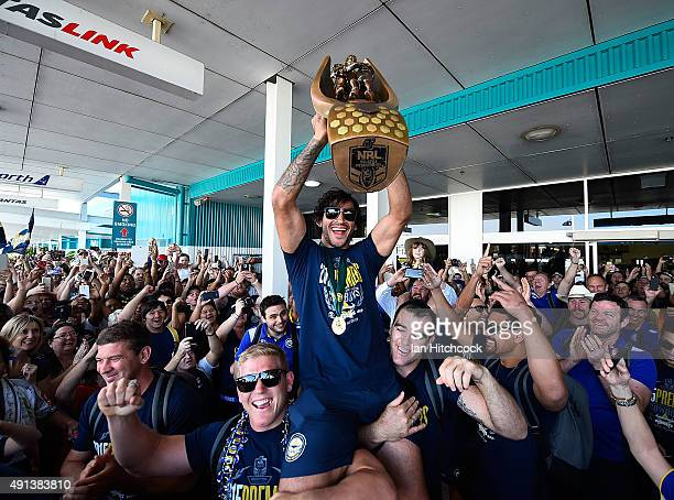 Johnathan Thurston of the Cowboys is hoisted onto the shoulders of Ben Hannant and Kane Linnett with the NRL trophy after arriving back at the...