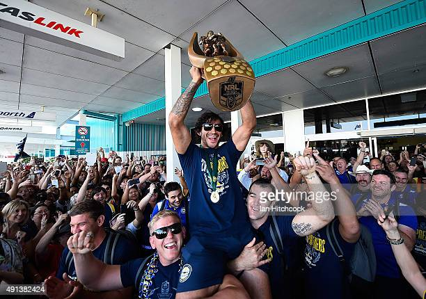Johnathan Thurston of the Cowboys is hoisted onto the shulders of Ben Hannant and Kane Linnett with the NRL trophy after arriving back at the...