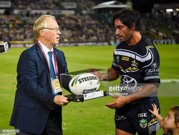 Johnathan Thurston of the Cowboys is presented with the game ball by NRL Chairman Peter Beattie after his 300th NRL game at he end of the round one...