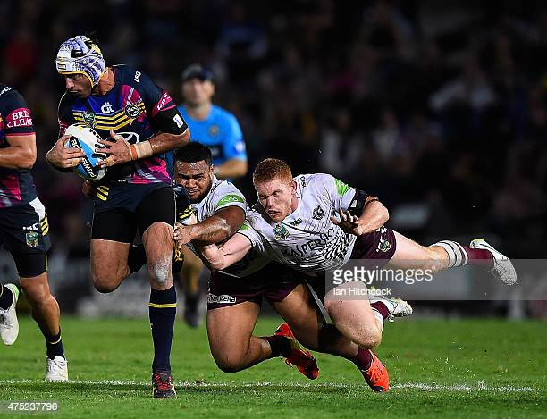Johnathan Thurston of the Cowboys is tackled by Dunamis Lui and Tom Symonds of the Sea Eagles during the round 12 NRL match between the North...