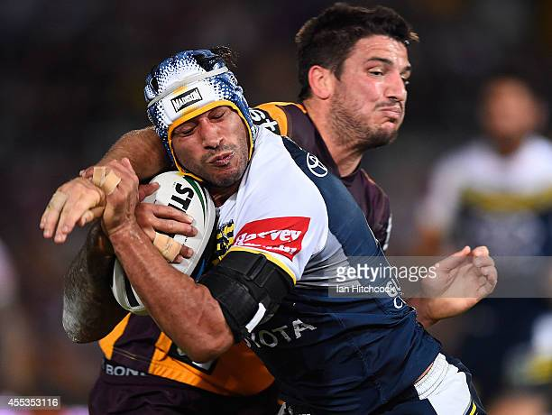 Johnathan Thurston of the Cowboys is tackled by Matt Gillett of the Broncos during the NRL 1st Elimination Final match between the North Queensland...