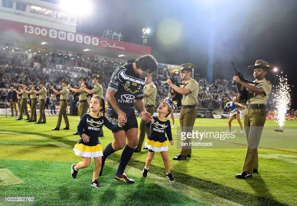 Johnathan Thurston of the Cowboys runs onto the field for his final home NRL match with his two daughters Frankie and Charlie during the round 24 NRL...