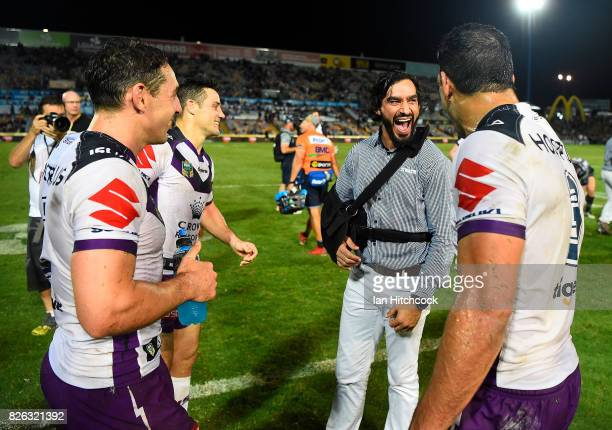 Johnathan Thurston of the Cowboys shares a laugh with Billy Slater Will Chambers and Cooper Cronk of the Storm during the round 22 NRL match between...