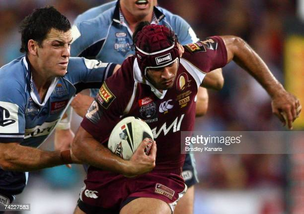 Johnathan Thurston of the Maroons attempts to break free from the tackle of Jarrod Mullens of the Blues during game one of the State of Origin series...