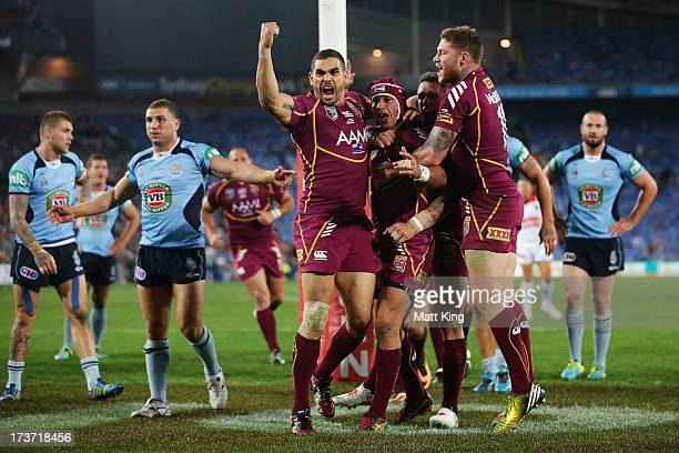 Johnathan Thurston of the Maroons celebrates with Greg Inglis after scoring the first try during game three of the ARL State of Origin series between...