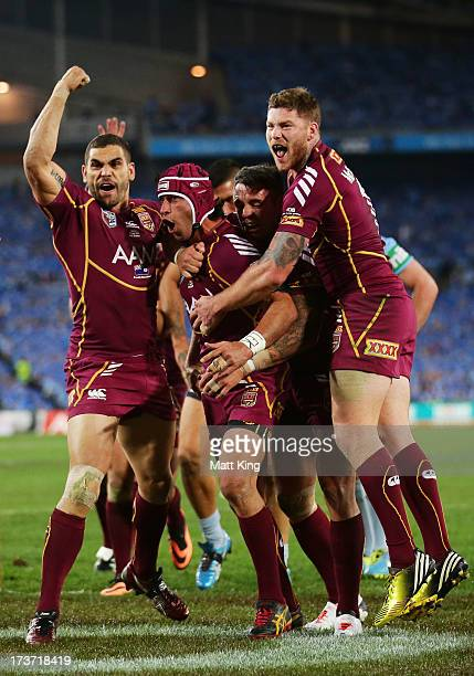 Johnathan Thurston of the Maroons celebrates with Greg Inglis and Chris McQueen after scoring the first try during game three of the ARL State of...
