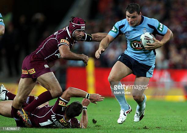 Johnathan Thurston of the Maroons injures his leg as his team mate Ashley Harrison of the Maroons lands on his as Anthony Watmough of the Blues...