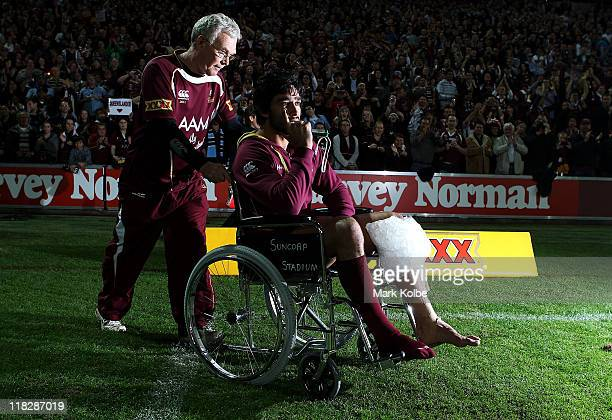 Johnathan Thurston of the Maroons is pushed onto the field in a wheelchair after the match after injuring his knee during game three of the ARL State...