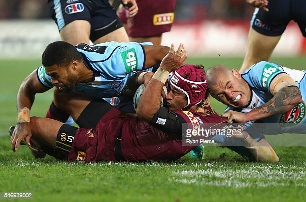 Johnathan Thurston of the Maroons is tackled by David Klemmer of the Blues during game three of the State Of Origin series between the New South...