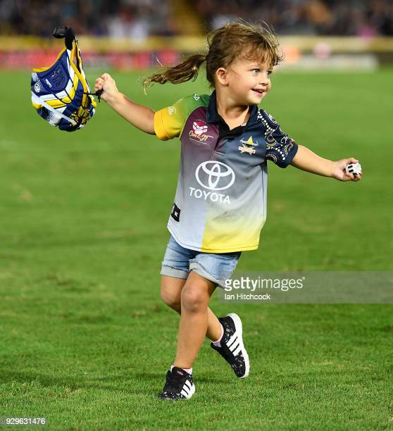 Johnathan Thurston's daughter Charlie runs with his headgear at the end of the round one NRL match between the North Queensland Cowboys and the...