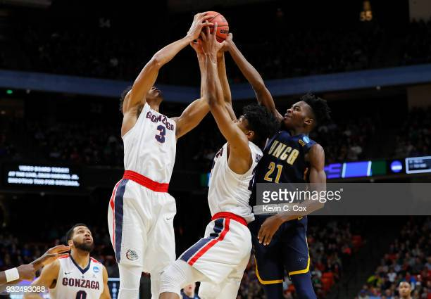 Johnathan Williams and Rui Hachimura of the Gonzaga Bulldogs battle for a rebound with James Dickey of the UNC-Greensboro Spartans in the first half...