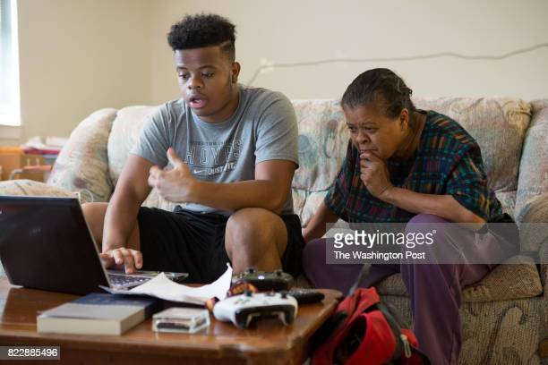 Johnathon Carrington works on a cover letter for a job application as his mother Valerie Carrington looks on at the family's apartment in the Tyler...
