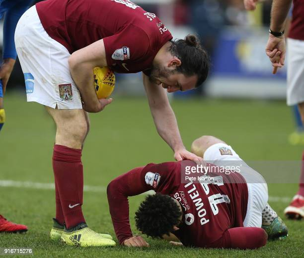 JohnJoe O'Toole of Northampton Town aids team mate Daniel Poweel during the Sky Bet League One match between AFC Wimbledon and Northampton Town at...
