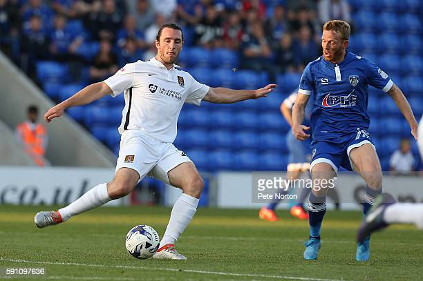 JohnJoe O'Toole of Northampton Town plays the ball watched by Paul Green of Oldham Athletic during the Sky Bet League One match between Oldham...