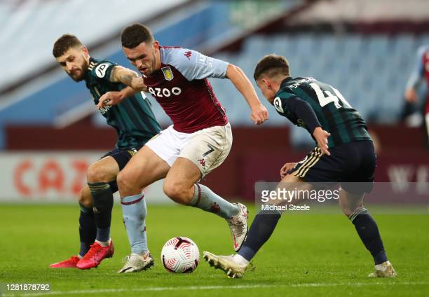John McGinn of Aston Villa is challenged by Mateusz Klich and Jamie Shackleton of Leeds United during the Premier League match between Aston Villa...
