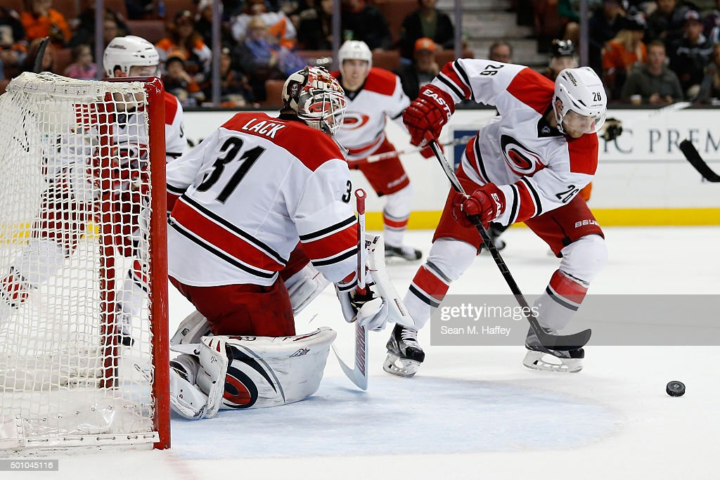 John-Michael Liles #26 of the Carolina Hurricanes and Eddie Lack #31 of the Carolina Hurricanes struggle with a loose puck during the third period of a game at Honda Center on December 11, 2015 in Anaheim, California.