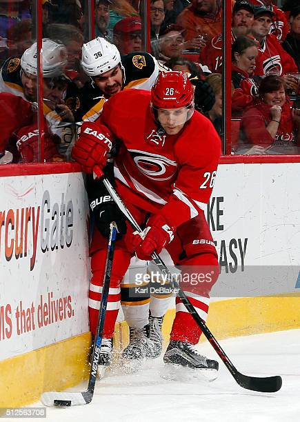 JohnMichael Liles of the Carolina Hurricanes checks Zac Rinaldo of the Boston Bruins during an NHL game on February 26 2016 at PNC Arena in Raleigh...