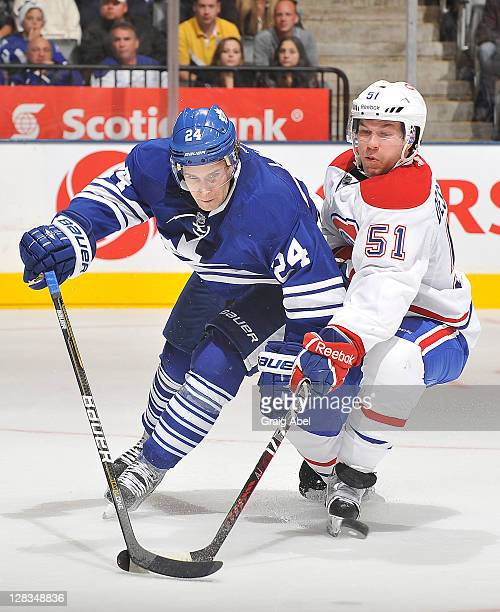 JohnMichael Liles of the Toronto Maple Leafs battles for the puck with David Desharnais of the Montreal Canadiens during NHL game action October 6...