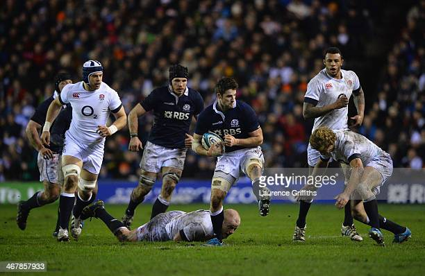 Johnnie Beattie of Scotland jumps the tackle of Dan Cole of England during the RBS Six Nations match between Scotland and England at Murrayfield...