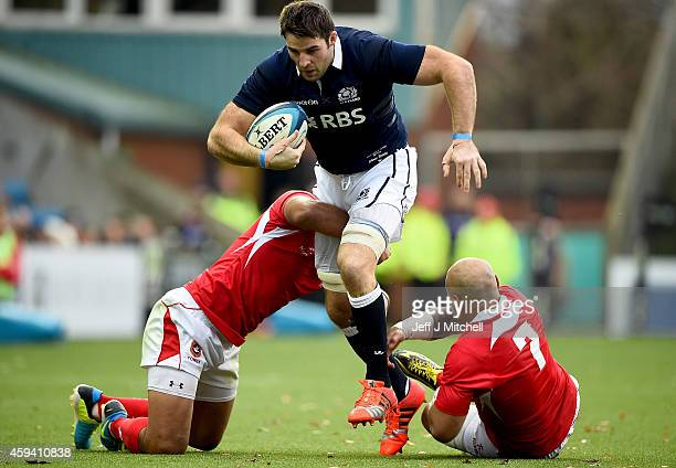 Johnnie Beattieof Scotland is tackled by Nili Latuand Siale Piutau of Tonga during the autumn test international match at Rugby Park on November 22...