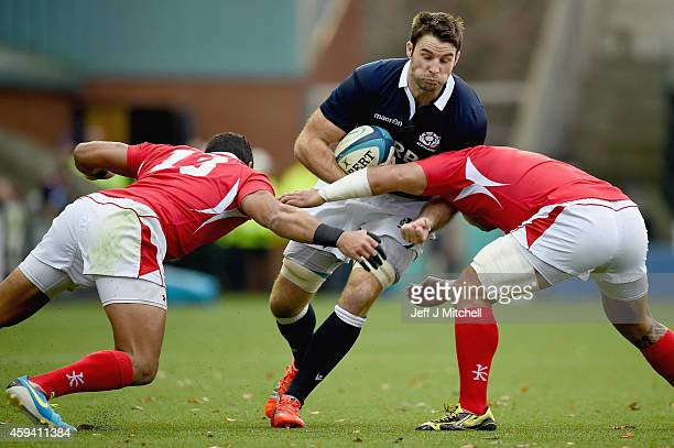 Johnnie Beattieof Scotland is tackled by Nili Latuand Siale Piutau and Vungakoto Lilo of Tonga during the autumn test international match at Rugby...